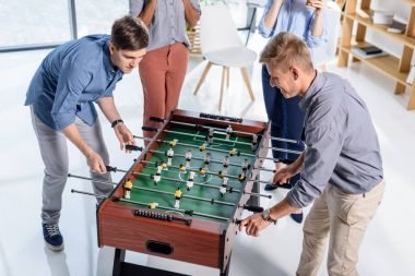 Business people playing table football in modern office