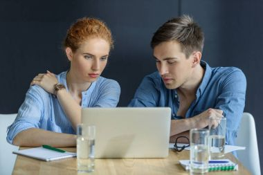 Thoughtful businessman and businesswoman working on project in modern office