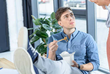 Young businessman eating chinese food during meeting break in modern office