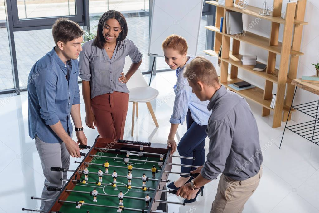 Coworkers team playing table football in modern office