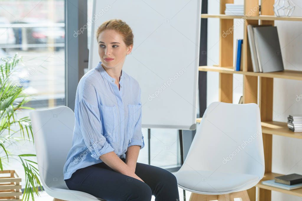Young businesswoman sitting on a chair in modern office