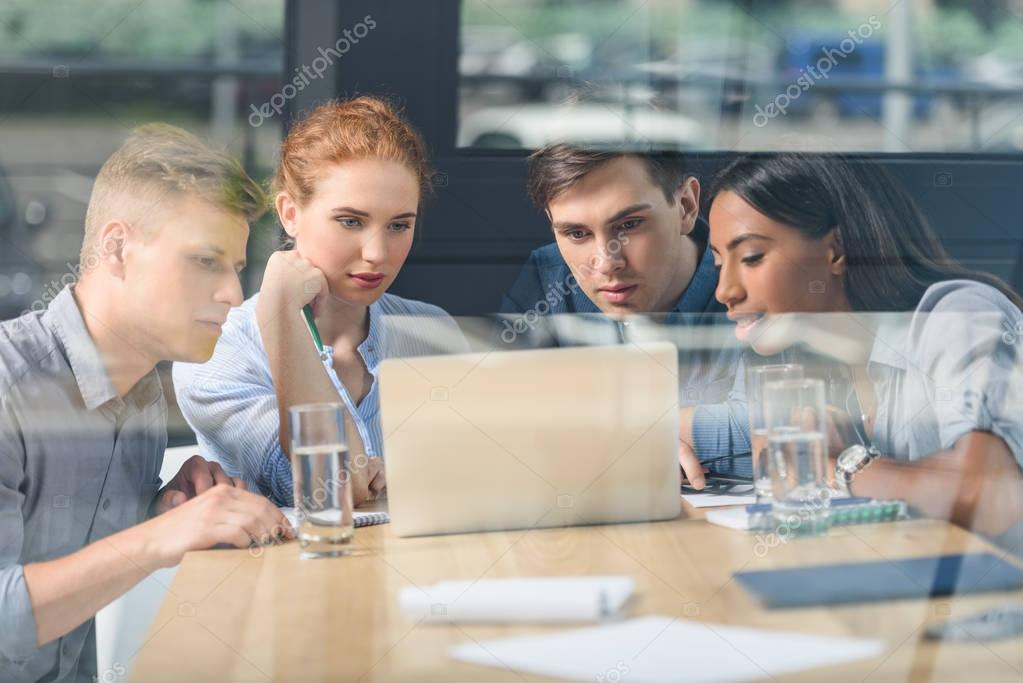 Behind the glass view of concentrated business people discussing project in modern office