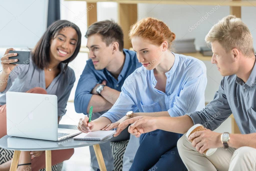 Diverse business team working on laptop in modern office