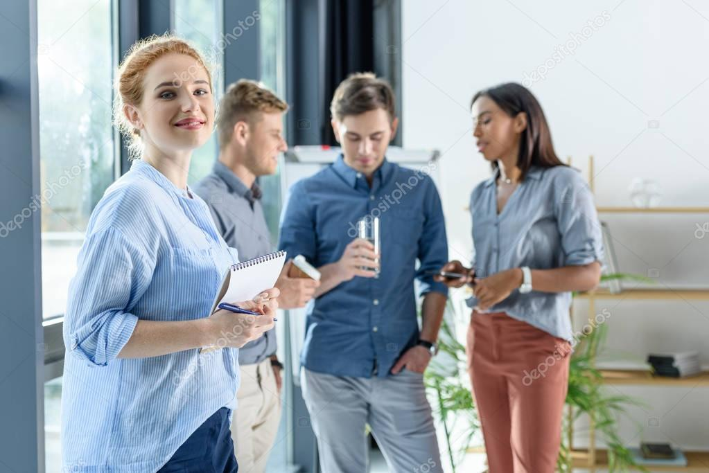 Young businesswoman with notepad in front of her colleagues discussing project in modern office