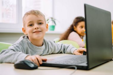 adorable little kid working with laptop on stem education class