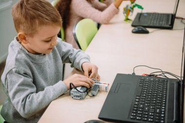 happy little kid making diy robot, stem education concept