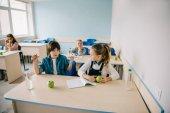 školačka naštvaný na svého spolužáka kvůli podvádění na lekci