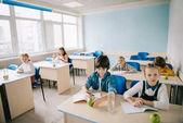 Gruppe von Kindern mit Äpfel und Wasser sitzen im Klassenzimmer