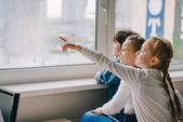 rozkošný školáci při pohledu na okna společně na učebně a směřující někam