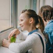 krásná školačka s čerstvým apple při pohledu přes okno v učebně