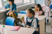 Fotografie adorable schoolchildren eating apples at classroom while having break