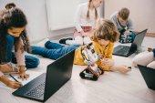Fényképek gyerek programozás laptopok ülve, a padlón, stem oktatási koncepció