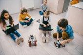Fényképek magas, szög, kilátás a gyerekek programozási robot ülve emeleten stem oktatási osztály