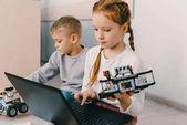 Teen školačka programování robota, zatímco sedí na podlaze s klukem