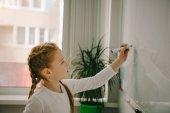 Photo happy little schoolgirl writing on whiteboard