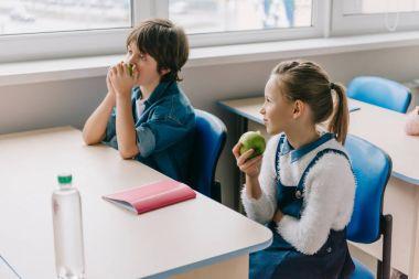 classmates sitting at desk and eating apples on break