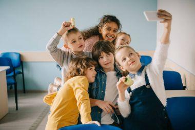 group of kids taking selfie at school classroom