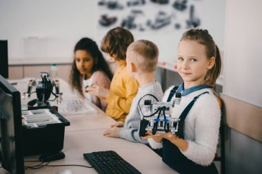 little kids with robots at stem educaion class