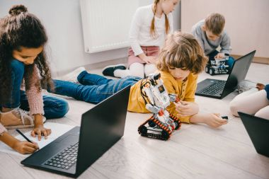 little kids programming with laptops while sitting on floor, stem education concept