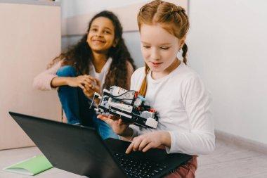 teen schoolgirls programming robot while sitting on floor