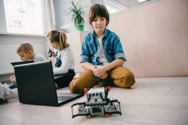 teen schoolboy with laptop and robot sitting on floor at machinery class