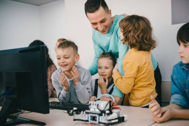teacher helping his teen students with diy robot on stem education class