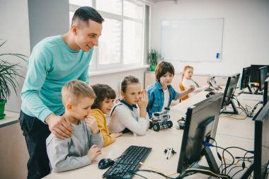 mutlu genç öğretmen kök Eğitim sınıf DIY robot ile onun genç öğrencilere yardım