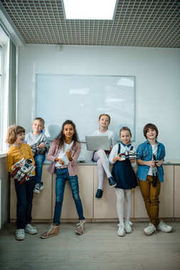 group of kids posing together with laptop and robots on stem education class