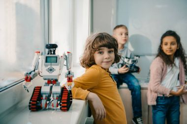adorable little schoolboy with diy robot on stem education class