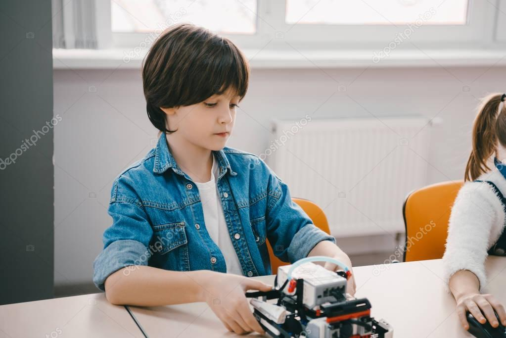 serious little kid making diy robot, stem education concept