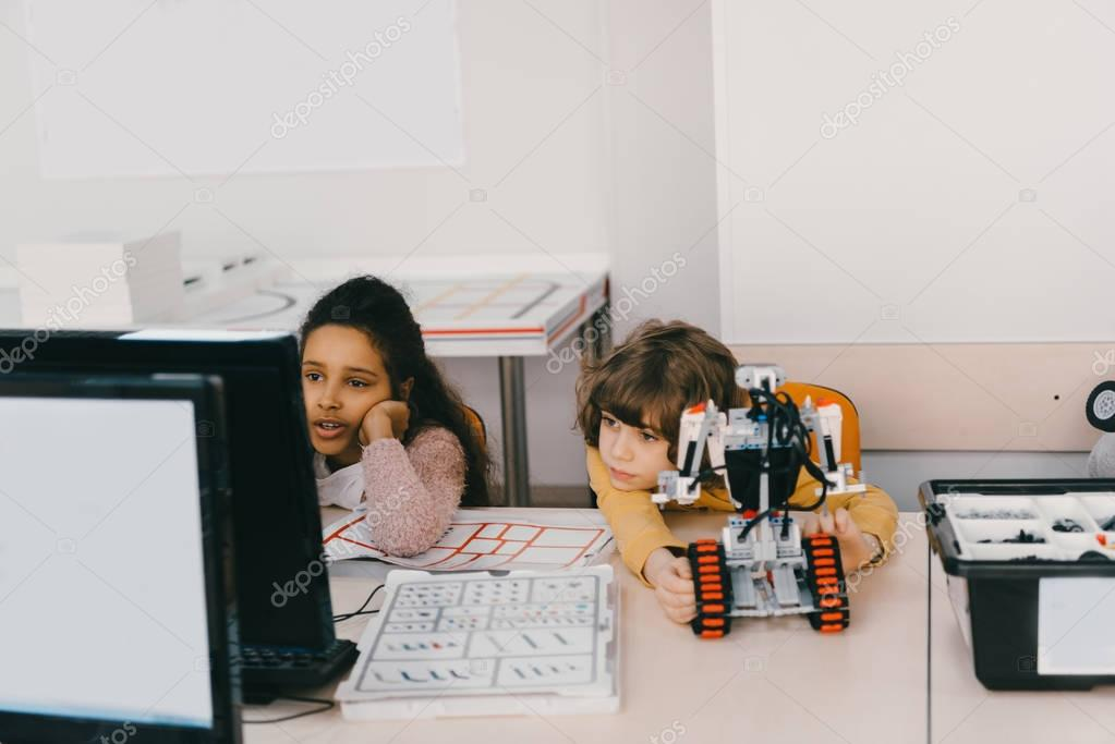 exhausted kids working with computer to programm robot, stem education concept