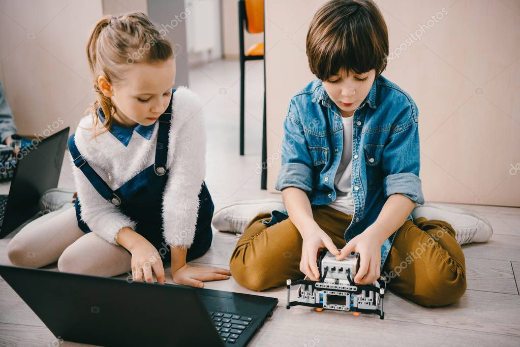 focused kids programming robot while sitting on floor at machinery class