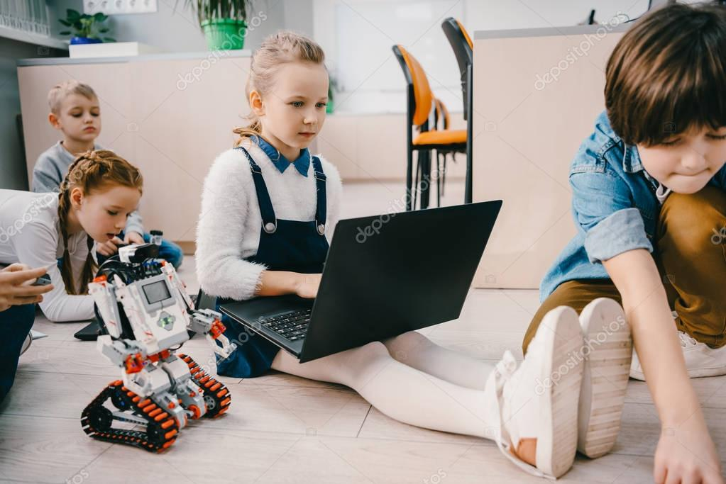 kids programming robot while sitting on floor at stem education class