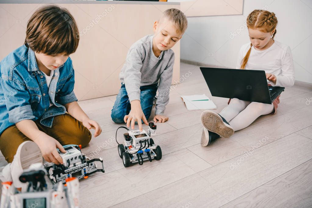 little kids sitting on floor at stem education class with robots and laptop