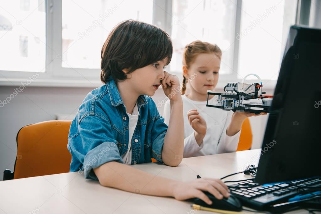 children programming robots together, stem education concept