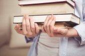 dítě hospodářství hromadu knihy