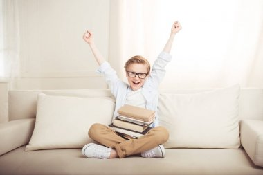 Happy little boy with pile of books sitting on sofa with raised hands stock vector