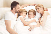 Fotografie happy caucasian family lying in bed
