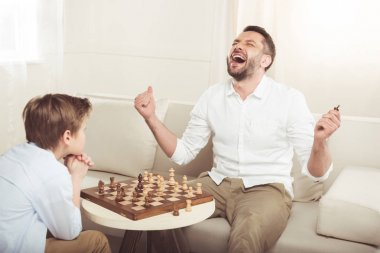 boy playing chess with father