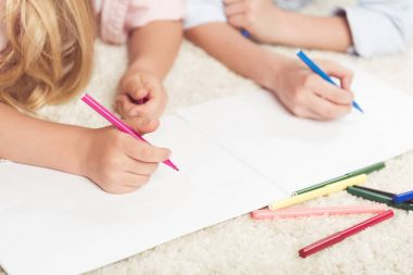 kids writing with felt pens on paper