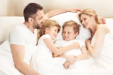 happy caucasian family lying in bed