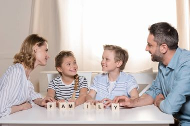smiling family sitting at table