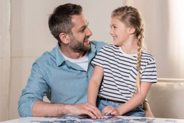 man playing puzzle with daughter