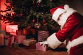 Fotografie santa with gifts under christmas tree