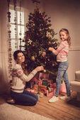 Anya és lánya karácsonyfát díszítenek