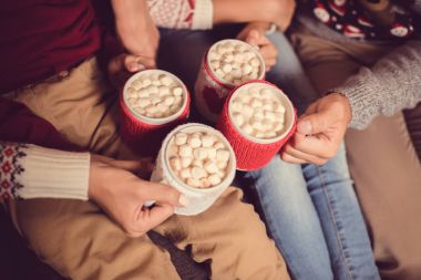 family with cups of cacao and marshmallow