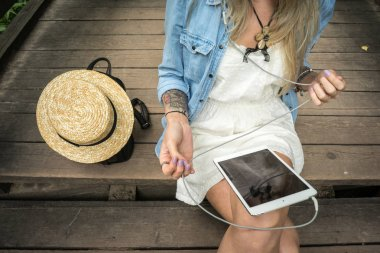 A young girl sits on wooden steps and holds a tablet in her hands, next to her is a leather backpack and a straw hat. The concept of a day off in nature