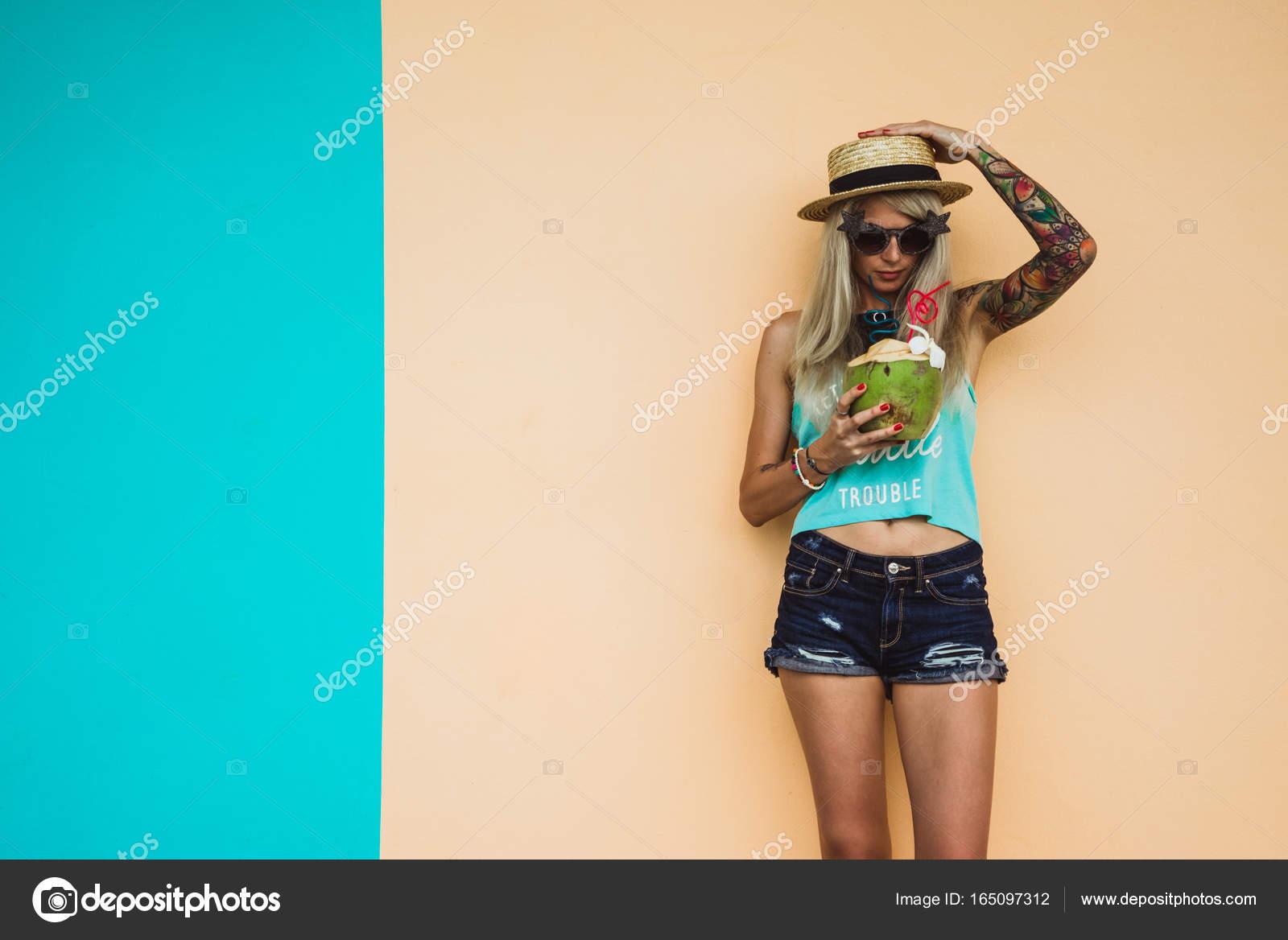 ec4225733c6 Όμορφη νεαρή ξανθιά hipster στο τζιν σορτς και ένα ψάθινο καπέλο ...