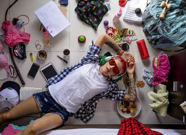 Student girl in a plaid shirt listening to music and thinking about the upcoming study at the University, lying on the floor. The mess in the ladies  room, the image of the modern girl student.
