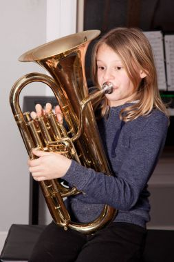 girl blowing baritone with crossed eyes